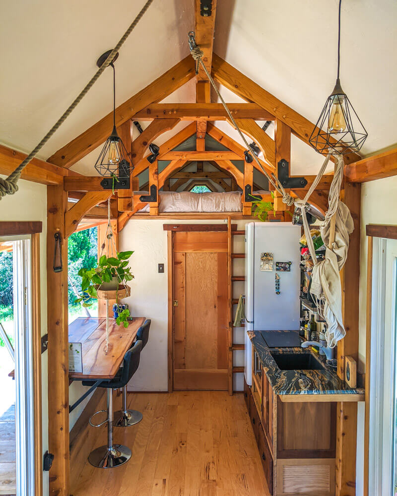 Timber Frame Tiny House on Wheels, The View looking at the kitchen, bar top and secondary loft
