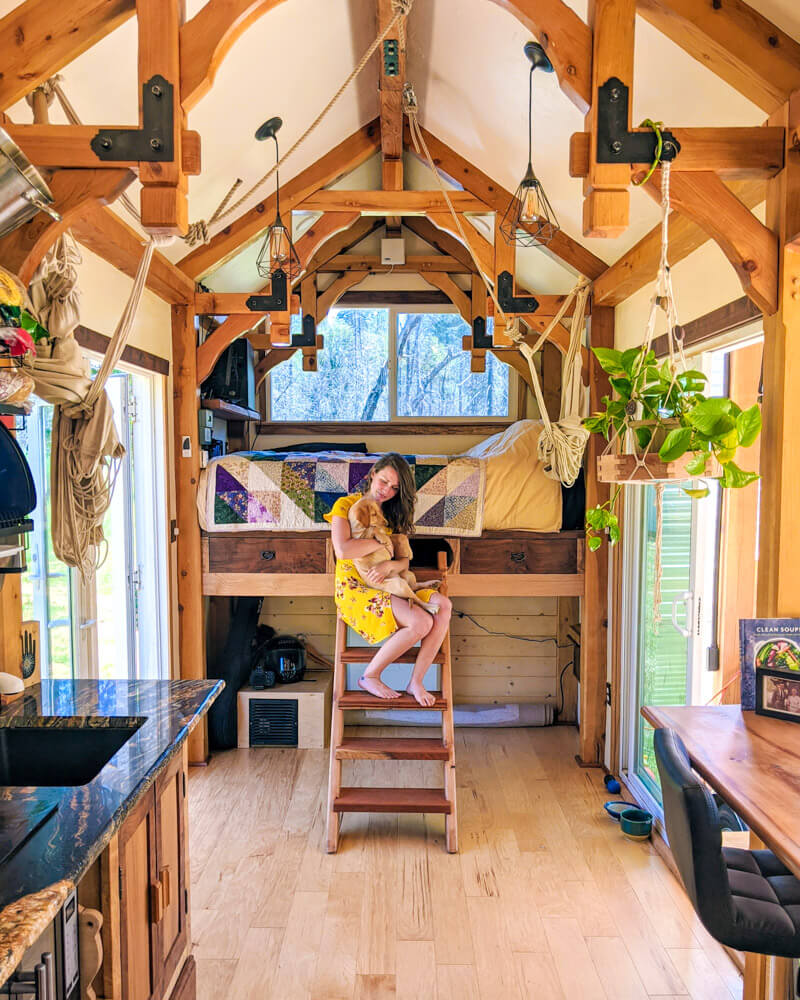 Timber Frame Tiny House on Wheels, Clara and Holding Whiskey on the Ladder Leading up to the master loft